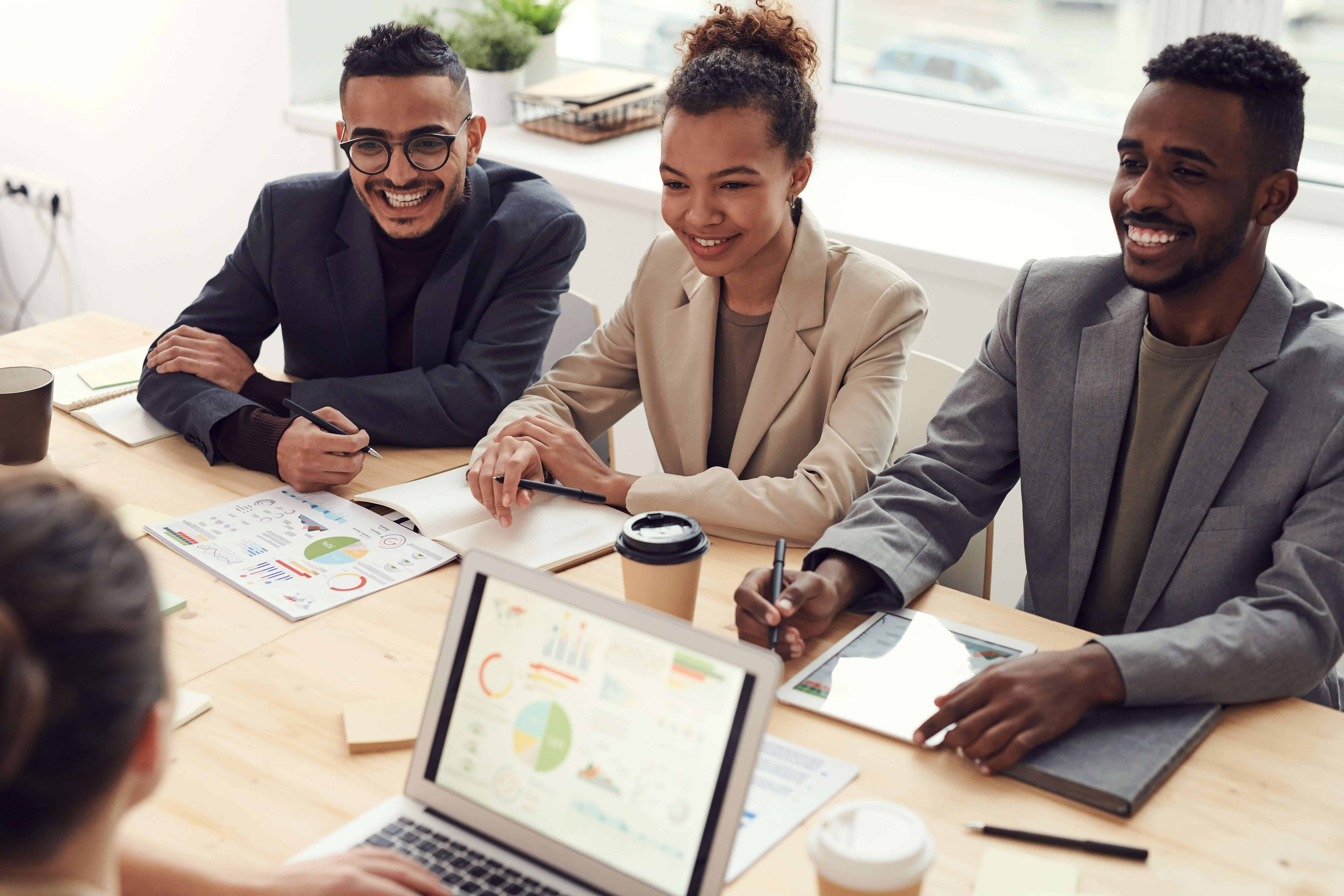 employee retention strategies - employees in a meeting sitting around a table smiling