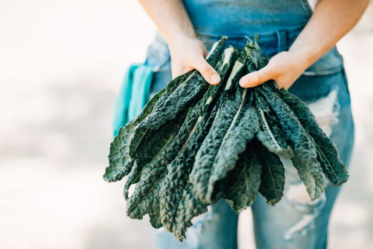 woman holding bunch of kale - The Best Foods for Anxiety and Depression